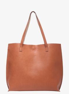 Sleek and chic, this oversized tote is made from cognac faux leather and has a detachable tan zip clutch inside. With a chic tan dual-side interior and a magnetic closure, the sexy bag can be folded over for a handheld look or worn reversible with the tan side exposed.Specially designed for you, the dual handles on top have been extended in length.