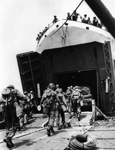 Members of a U.S. combat engineer unit march aboard a Landing Ship-Tank, or LST.