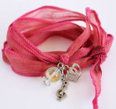 Your kids can craft plenty of these easy and Charming Wrapped Silk Ribbon Bracelets for all their holiday gift giving.  Each one can be customized by creating and adding charms for each recipient, making this simple homemade Christmas gift a personal