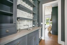Well appointed gray butler's pantry features glass front cabinets fixed on either side of stacked floating gray shelves mounted to mini marble subway backsplash tiles above a wall mounted polished nickel faucet.