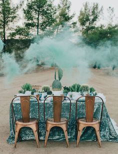 Velvet tablecloths can add eclectic vibes to a wedding reception. The glam of the blue plush fabric contrasts beautifully with the rustic chairs, smoke bombs and greenery of this modern boho wedding decor. | Luxurious Velvet Details for Wedding Inspiration