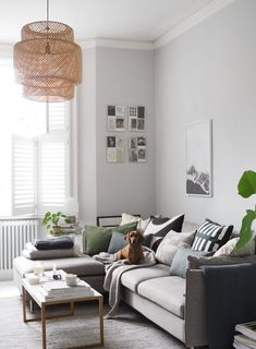 Grey Scandinavian style living room with L-shaped sofa and monochrome details. How does our childhood home influence our interior style?