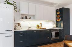 Elegant kök med inredning från Ballingslöv utrustad med påkostade vitvaror från SMEG. Klassisk bänkskiva i vit stenkomposit som vackert bryter av mot de tvåfärgade köksskåpen.