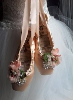 Altered Embellished Ballet Pointe shoe, These new peachy pink satin ballet pointe shoes have been embellished with diamantes, tulle flowers, french trim and velvet blooms and leaves. The insole features vintage ballerina and music manuscript which results in a vintage inspired shabby chic unique ballet shoe for the lover of dance. Purely a decorative item this pair would look lovely hung on a wall, a door knob, mirror or dress form or placed on a dressing table for a romantic whimsical…