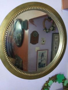 A round wood gold mirror with decorative gold wood frame