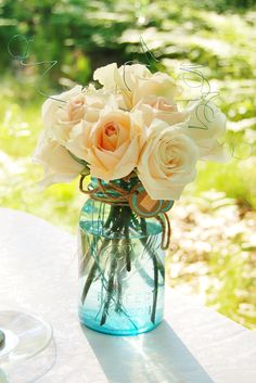 Blue ball jar with peach roses for a farm to table dinner.