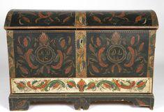 Kiste med buet lokk og  løssokkel. Rosemalt lokk og tre sider. Innsiden av lokket og leddik også malt. Angivelig malt av Per Svalde fra Telemark. Han reiste til Amerika i slutten av 1840 årene.