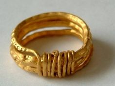 Gold finger-ring consisting of a triple coil of thick, lozenge-section wire, the front and sides decorated all along the ridge with punched, back-to-back crescents, and small triangles at the tapering ends; the ends are drawn into thin wires wound vertically round the coil in 8 turns at the back of the hoop.