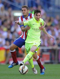 Lionel Messi of FC Barcelona is fouled by Koke Resurreccion of Club Atletico de Madrid during the La Liga match between Club Atletico de Madrid and FC Barcelona at Vicente Calderon Stadium on May 17, 2015 in Madrid, Spain.