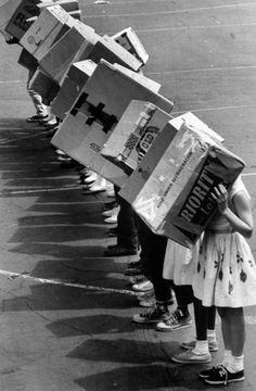 <b>Caption from LIFE.</b> Fifth-graders at the Emerson School in Maywood, Ill. line up with backs to the sun and their eclipse-watching boxes over their heads.