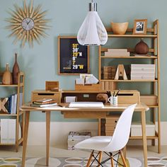 Mid-century-style furniture and duck-egg blue walls give this home office a retro feel. Striking accessories such as the starburst clock and pendant light are stylish as well as practical