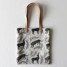 """Large natural linen tote with light colored leather straps  Screen printed with non-toxic black ink  Lined with 100% cotton canvas  Inside pocket  Brass rivets  About 14 x 15""""  Leather will darken and soften with wear  A sturdy carry-all to accompany you on your daily adventures to the market,  the beach or the coffee shop!"""