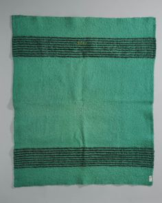 Groene babydeken met zwarte strepen en geborduurde initialen. Bovendeken waarin bakerkindje gewikkeld is doorgaans groen met zwarte strepen. Hieronder nog rode deken met zwarte strepen. Beide dekens omboord met groen of rood band. Groene dekens werden ook in wieg gebruikt, dus mogelijk is dit exemplaar niet gebruikt voor inbakeren. Wanneer men met kindje uit wandelen ging gebruikte men over groene deken vaak nog witte met rode strepen die afgezet is met rood band. 1850-1940 #NoordHolland…