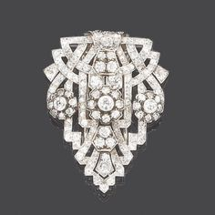The tapered and slightly convex plaque of openwork geometric form, set throughout with old brilliant and single-cut diamonds and mounted by three slightly graduated, similarly set floral clusters, diamonds approx. 4.40ct. total, length 4.8cm.