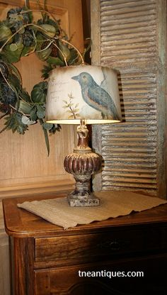 A lamp with a painted bird shade featured with an antique French shutter