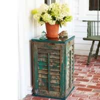 outdoor side table made out of four window shutters and a glass top.