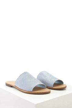 A pair of faux suede slides featuring a slip-on style and a low stacked heel.