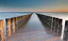 golfbrekers op het strandDoor de lange sluitertijd wordt het water mooi glad.