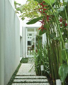 Pequeno jardim com plantas tropicais e piso de pedras portuguesas.  Fotografia:   http://www.decorfacil.com