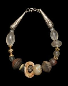 by Marion Hamilton | Necklace; Silver beads Yemeni, rock crystal wedding beads Afghanistan, clay spindle whorls Mali amber Morocco, rock crystal seal Afghanistan, all 19th c., prehistoric stone bead in center, hard stone pi disk contemporary, 22K gold beads India || $3500