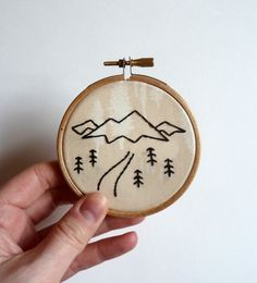 Mini mountain landscape sketch embroidery hoop. The design is embroidered using back stitch with black DMC thread, on Art gallery fabrics
