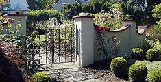 A wrought iron gate is in keeping with the Spanish style wall.