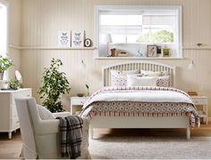 Soveværelse i landlig stil med en stor hvid seng, 2 hvide sengeborde, en hvid kommode med 3 skuffer og 2 hvide garderobeskabe.