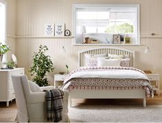 Dormitorio rústico con una cama grande, dos mesillas de noche, una cómoda de 3 cajones y dos armarios, todo en blanco.