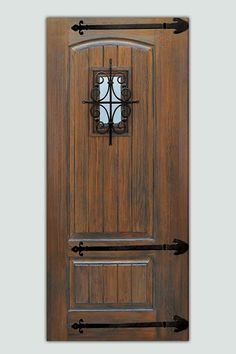 Dark stain, optional iron strap hinges, and a speakeasy-style window grille give this V-grooved slab door its rustic Spanish-Mission look. About $1,735 from gcdoor.com | thisoldhouse.com