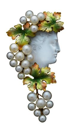 An Art Nouveau Bacchante Moonstone jewel, circa 1880, probably American. The carved cameo moonstone head of a Bacchante facing towards the right in profile, her wavy hair crowned with greenish reddy golden enamelled vine leaves amidst clusters of natural pearl grapes cascading over her shoulder, the reverse also decorated. #ArtNouveau #jewel