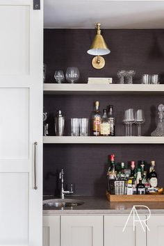 Jason Arnold Interiors - Concealed behind a sliding white door completed with an aged brass handle, this hidden wet bar boasts a Boston functional library wall light mounted on black grasscloth fitted with floating light gray shelves.