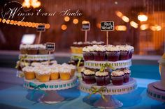Vintage style cake stands woven with colorful ribbon display assorted cupcakes with chalkboard flavor signs