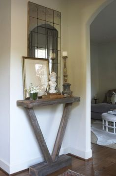Enhance an empty corner with a vignette created from a reclaimed wood table topped with a metal accessory, even if it's just a photo frame.