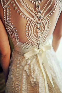 robe de mariée à froufrous, dos en tulle brodé et décoré de strass et un ruban en satin