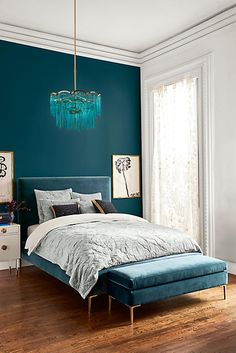 Anthropologie Teal statement wall, light fixture, and bed frame with gold accents, and white furniture
