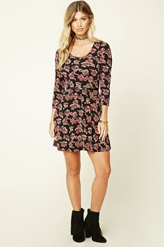A textured knit skater dress featuring a floral print, removable faux leather belt, scoop neckline, and 3/4 sleeves.