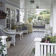 This is a beautiful Front Porch with its lovely white Wicker furniture,light fixtures & plants.