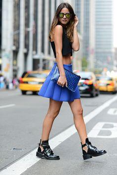 Acheter la tenue sur Lookastic: https://lookastic.fr/mode-femme/tenues/top-court-noir-jupe-patineuse-bottines-chelsea-pochette/2372 — Top court noir — Pochette en cuir géométrique bleue — Jupe patineuse bleue — Bottines chelsea en cuir noires