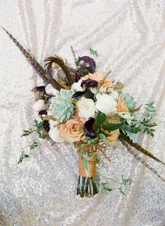 super textural bouquet, love the pheasant feathers and gold wrap.