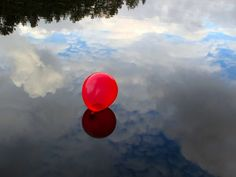 red balloon and cloud reflection