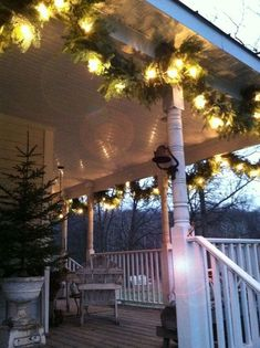 Hanging lighted garland on ceiling of covered porch. Christmas tree in urn