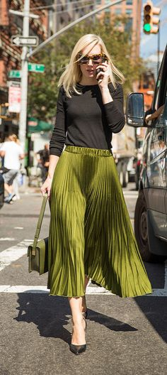 A full pleated skirt, black shirt, and olive leather purse