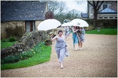 running bridesmaids with umbrellas