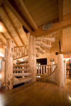 Custom half log spiral staircase with hand scraped wood railing to loft from great room, and mirrored log spiral staircase to basement.
