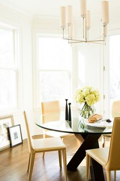 Chic dining room boasts a Ziyi 8 Light Chandelier illuminating a round glass top dining table lined with butter yellow leather dining chairs.