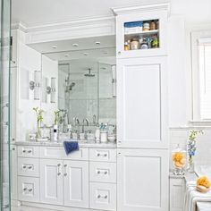 To-the-ceiling cabinets on each side help keep this shared bathroom vanity clutter-free.