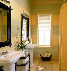 Bold Bath - Sage green and sunny yellow paint wrap this narrow bath in 18-inch-wide horizontal stripes. Pedestal sinks with wide-set lavatory  fixtures in satin nickel, mirrors in bamboo-style frames, and contemporary lighting complete the space.