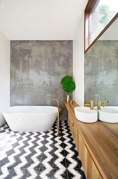 Airy bathroom with printed tile floors, a freestanding tub and gold fixtures