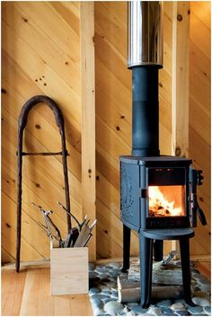 I love these little wood stoves/heaters. I would like to have several in my cabin. I really like the use of river stones under the stove as a heat shield, too.