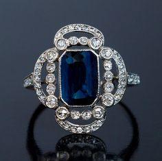 Un anillo de platino Art Deco temprano, alrededor de 1915, centrado en un zafiro natural azul situado en un marco de apertura festoneado adornado con el viejo single y diamantes de la rosa cortada.
